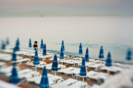 Row of beach umbrellas in a beach resort of Nice -created with lensbaby photo