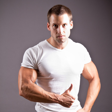 cooky: young muscular man flexing his muscles Stock Photo