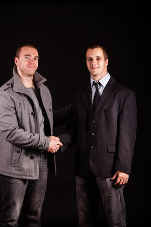 Two young businessman shaking hands photo