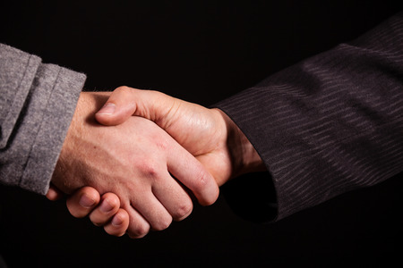 Two businessman shaking hands over black photo