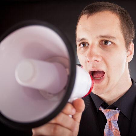 bawl: businessman shouting through megaphone in studio Stock Photo