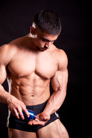 steroids: young bodybuilder taking steroids over black Stock Photo