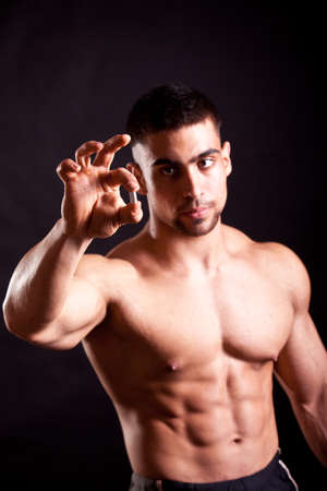 pectorals: young bodybuilder taking steroids over black Stock Photo