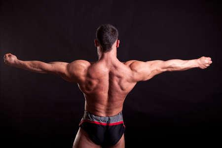 lats: young bodybuilder posing in studio