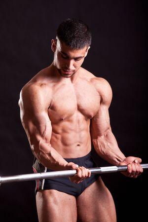 pectorals: young bodybuilder traininig over balck background