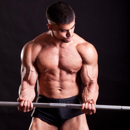tricep: young bodybuilder traininig over balck background
