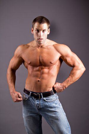 young muscular man flexing his muscles photo