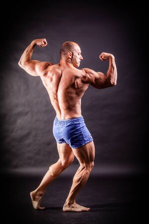 flexing: bodybuilder flexing his muscles over black background Stock Photo