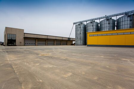 silos: Cereal silos with a yellow building Stock Photo