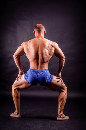 sixpacks: bodybuilder flexing his muscles over black background Stock Photo