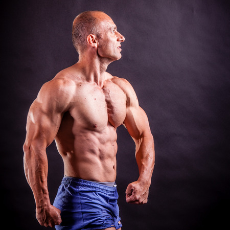 pectorals: bodybuilder flexing his muscles over black background Stock Photo