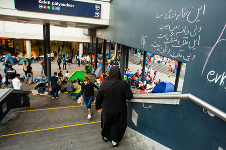 assad: BUDAPEST - SEPTEMBER 4 : War refugees at the Keleti Railway Station on 4 September 2015 in Budapest, Hungary. Refugees are arriving constantly to Hungary on the way to Germany. Editorial