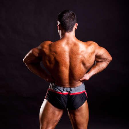 muscle guy: young bodybuilder posing in studio