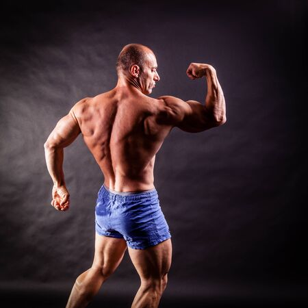 bodybuilder flexing his muscles over black background Stock Photo