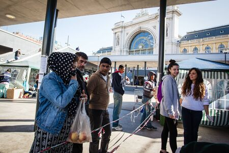 poorness: BUDAPEST - SEPTEMBER 7: war refugees reading go Wien text at Keleti Railway Station on 7 September 2015 in Budapest, Hungary. Refugees are arriving constantly to Hungary on the way to Germany. Editorial