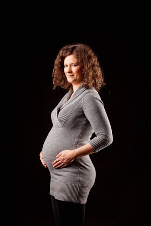 bellybutton: beautiful pregnant young woman in studio