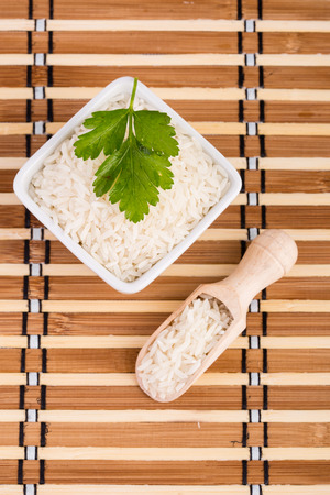 uncooked: Uncooked jasmin rice in a wooden spoon