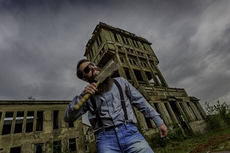 cleaver: handsome man lick cleaver with old building Stock Photo