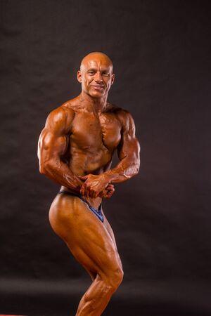 steroid: bodybuilder posing over black background Stock Photo