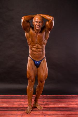 bodybuilder posing over black background photo
