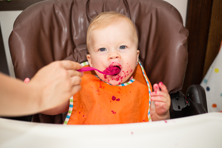 smeared baby: baby girl eating beetroot at home Stock Photo