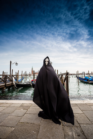 speculative: Woman in dark halloween like costume on streets of Venice during carnival Stock Photo