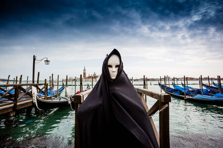 Woman in dark halloween like costume on streets of Venice during carnival Stock Photo