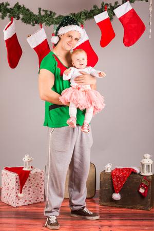 funny Christmas elf with baby girl in studio