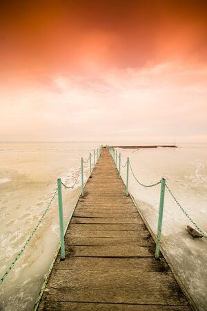 frozen lake Balaton with beautiful sky and footbridge