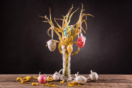 Wilted bouquet of yellow tulips with easter eggs Stock Photo