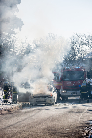 PECS, HUNGARY - JANUARY 21: Burning Car on road Pecs in wintertime, Hungary on January 21, 2017.