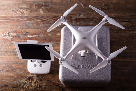 PECS, BARANYA, HUNGARY - MARCH 1, 2017: Brand new DJI Phantom 4 pro quadcopter drone with controller and ipad air 2 wooden studio background