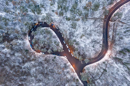 aerial view of curvy road with snowy forest