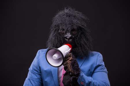 businessman wearing gorilla mask and screaming to megaphone Stock Photo