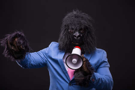 businessman wearing gorilla mask and screaming to megaphone