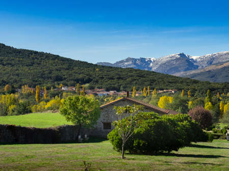 Landscape of the Sierra de Avila in early autumn with the Gredos mountains in the background and with blue sky.