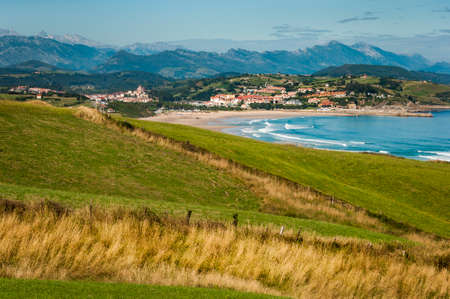 Landscape of the coast of Cantabria with a green hill in the foreground and the village of San Vicente de la Barquera and the Picos de Europa mountains in the background.