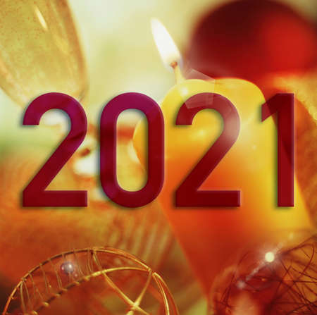 Year 2021 on a background of Christmas elements in warm tones and slightly out of focus.