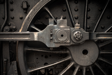 Old steam engine train wheels and parts close-up photo