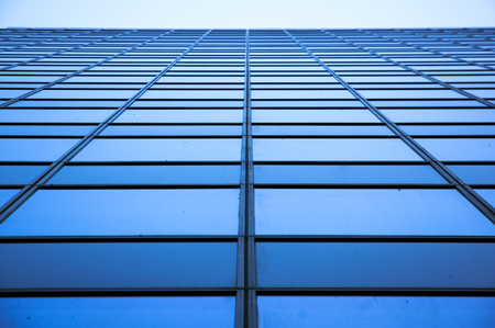 Blue glass and metal office building balanced perspective shortening windows on blue sky