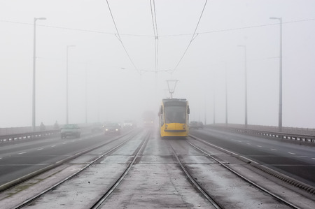 Yellow tram comes in the mist in the bridge Stock Photo