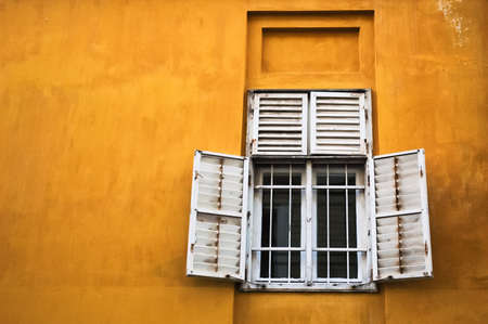 Old shuttered wooden window on orange yellow wall