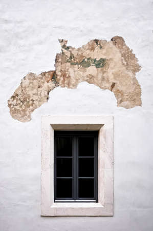 Little old white window with white stone frame on peeled plaster white wall