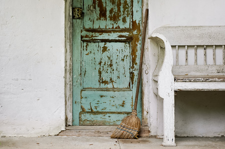 Rural mood  Green door, white wall an old bench, broom Stock Photo