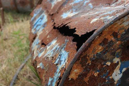 Rusty old holey metal barrel at dumpsites