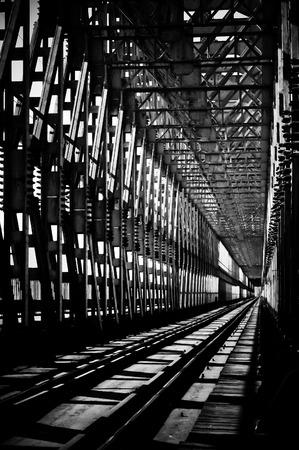 Old rusty metal railway bridge, black and white