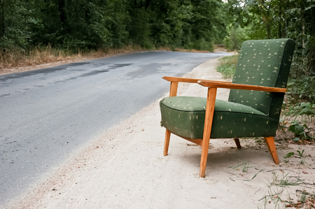 Old green chair on the edge of the abadoned road Stock Photo