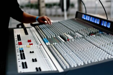 A hands above professional audio mixing console with faders and adjusting knobs for radio and TV broadcasting