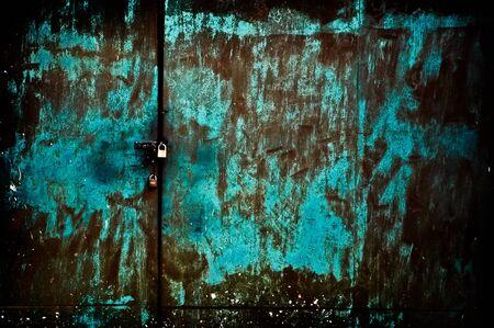 Abadoned closed green rusty door with yellow padlock