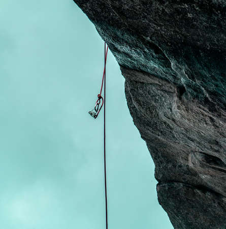 Belay Device Dangling from a Rope on the Side of a Cliff Stock Photo